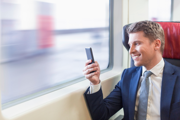 Man sitting on train smiling at mobile