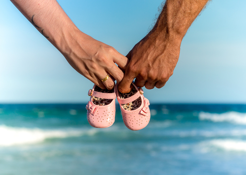Couple holding a pair of baby shoes