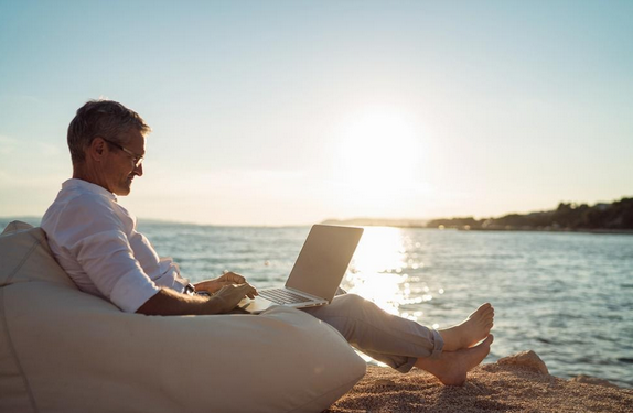 man with laptop on lap sitting on the beach